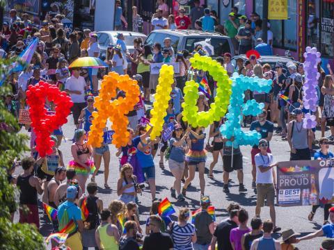 Gente celebrando con globos de colores durante el desfile Denver Pridefest