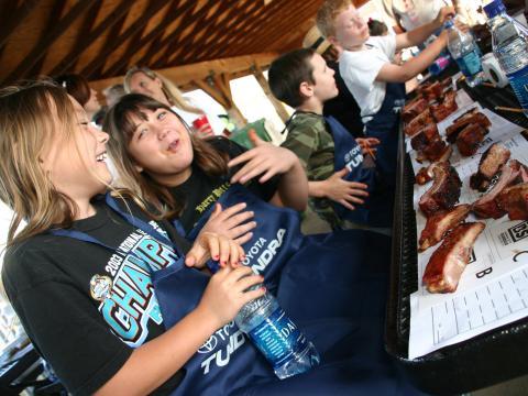 Niños disfrutando de costillas durante el WhistleStop Bar-B-Que Weekend en Huntsville, Alabama