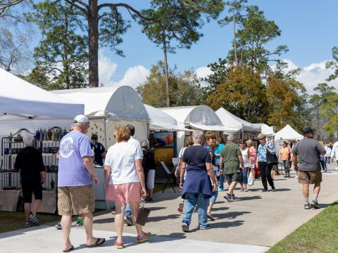 Clientes paseando por los puestos de artistas en el Orange Beach Festival of Art en Alabama